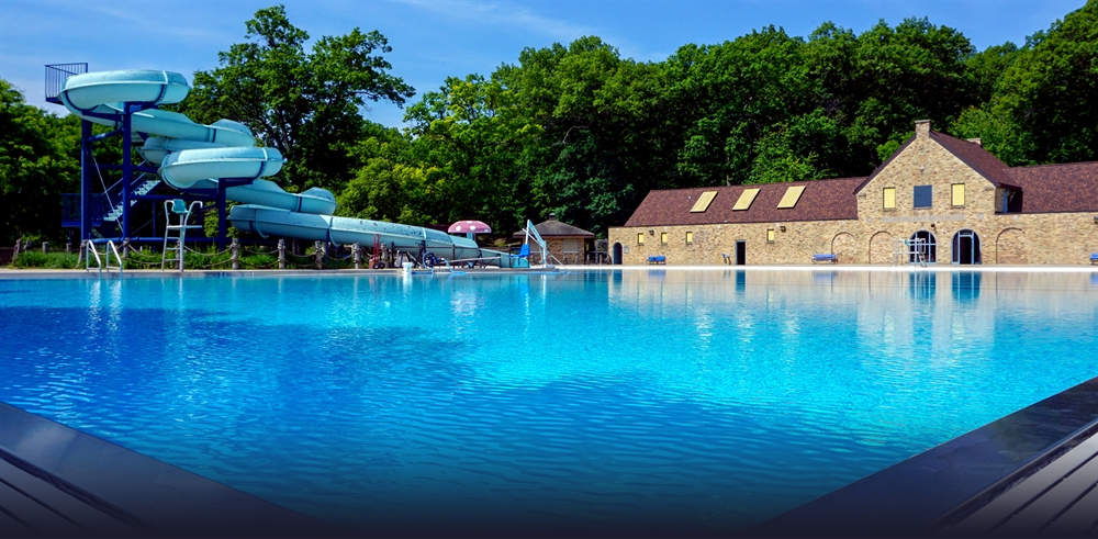 Photo of Richmond Park pool with the administrative building and water slide in the background