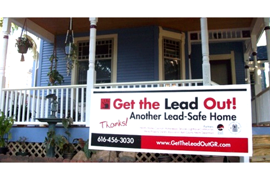 Photo of the front porch of a home with a sign reading,
