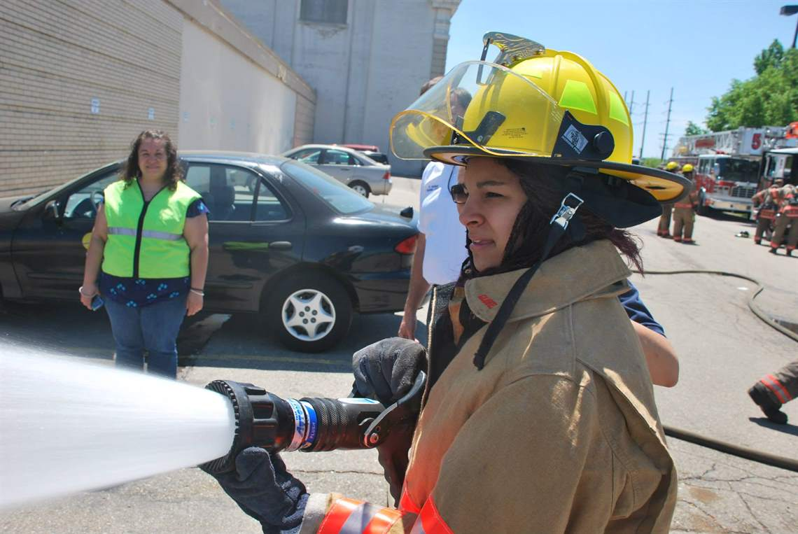 Young woman in the community holding fire hose and spraying water during the Fire Fighter for a Day event.