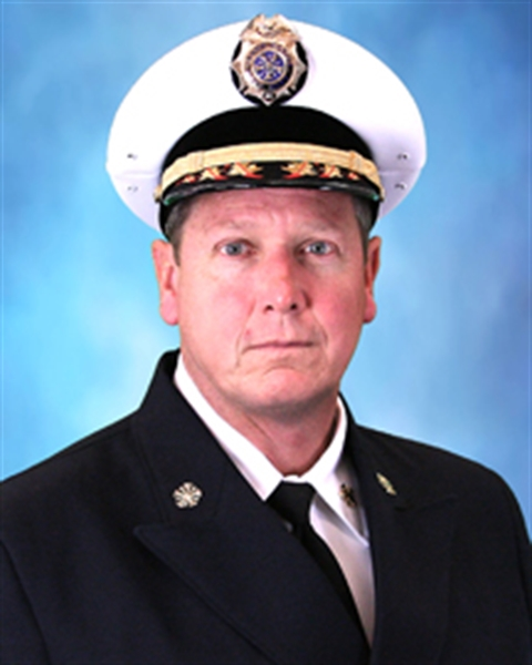 Picture of Fire Chief John Lehman in uniform with blue background