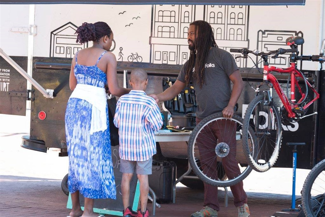 Image of Spoke Folks mobile bike repair station with an employee helping out a mom and son