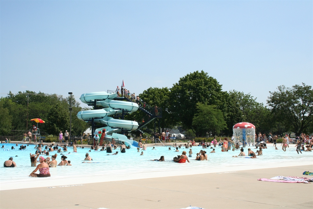 Image of people enjoying Richmond Park Pool, waterslide, and water fountains.