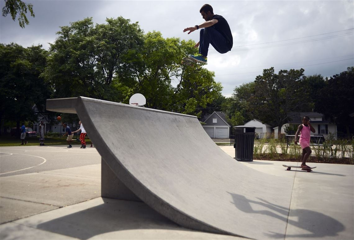 photo of teenage boy mid air doing skateboard tricks on a skateboard ramp