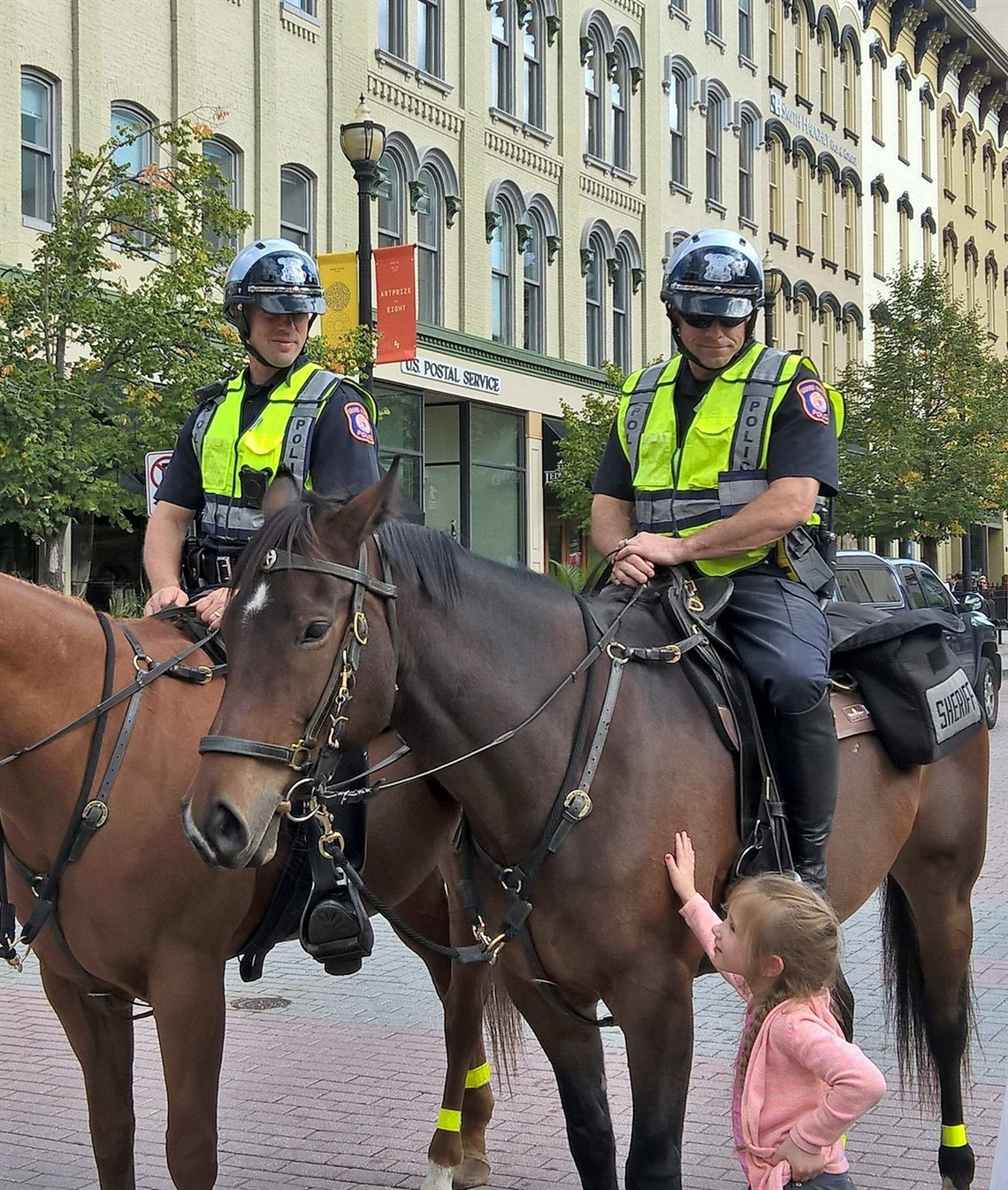 Two officers on horses with little girl