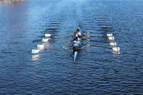 Picture of the GVSU rowing team in action. They are on the river and are at the center and focal point of the picture.