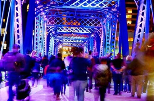 Blue bridge with purple lighting. People are walking along the bridge but are blurred in the image.