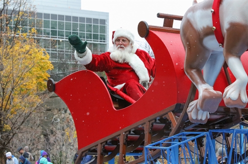 A picture of Santa in his sleigh from the 2017 Art Van Santa Parade. He is waving at the crowd.