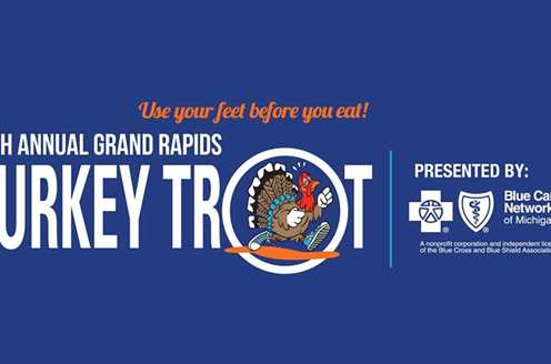Banner for the 26th annual Grand Rapids Turkey Trot. This blue banner features text describing the event with a cartoon turkey running in the O of trot. The tag line