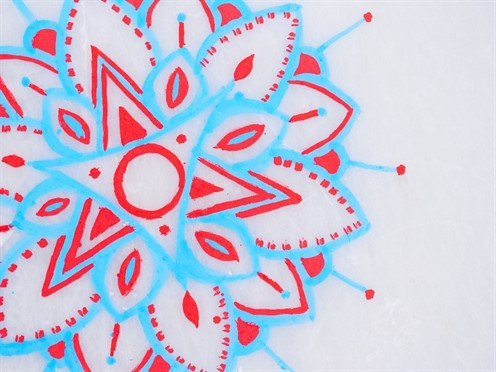A blue and red mandala that has been painted on the ice.