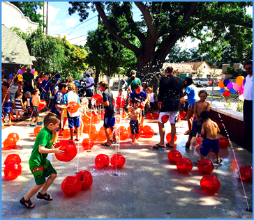 Photo of children playing on a splash pad with balloons in a City park