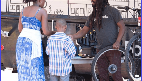 Image of a bike mechanic assisting a parent and child with bike repair