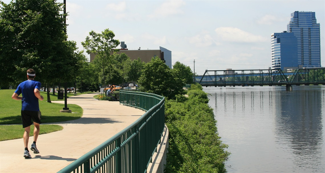 picture of runner jogging on paved trail alongside Grand River