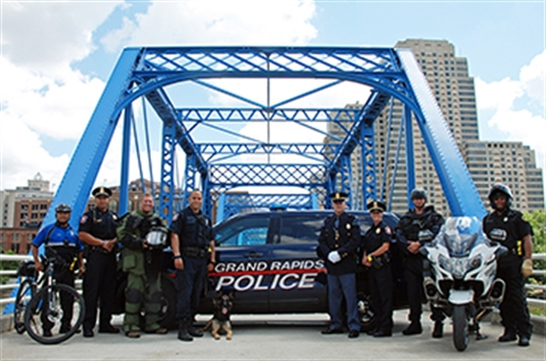 Grand Rapids police officers assembled in a group photo at the Blue Bridge