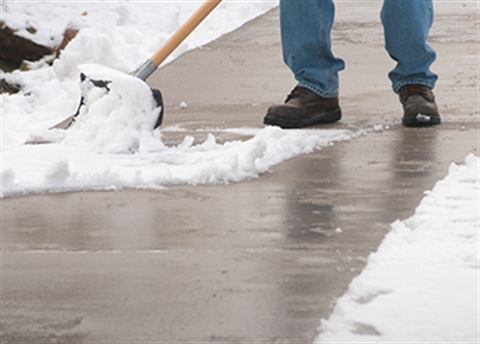 Close up photo of a person shoveling a sidewalk